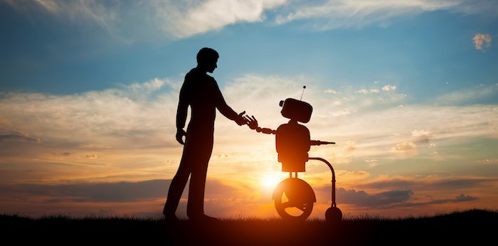 Man shaking robots hands in the sunse