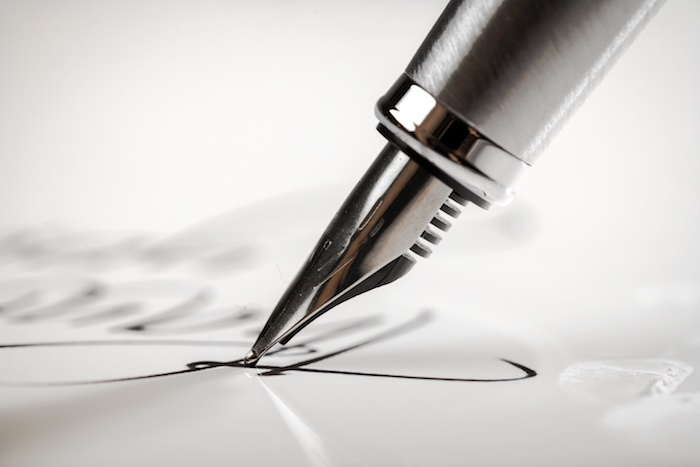 Silver pen signing a paper