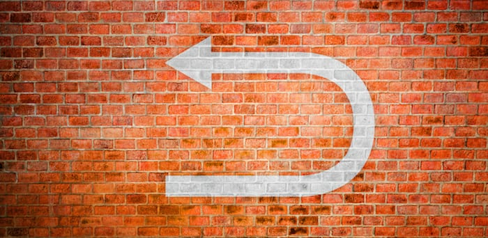 White turnaround sign on vintage brick wall, Decision making concept