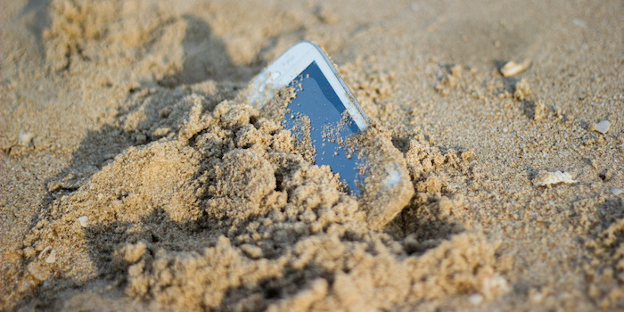 phone dropped deep in the sand at the beach