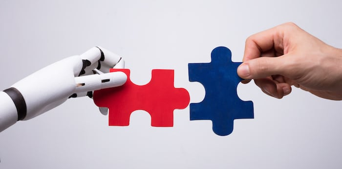 Close-up Of Robot And Human Hand Holding Red And Blue Jigsaw Puzzle